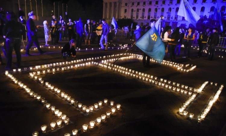 Young Crimean Tatars with the Crimean Tatars blue flags light candles in a form of their Crimean Tartar peoples' symbol during a rally requiem in Crimea.