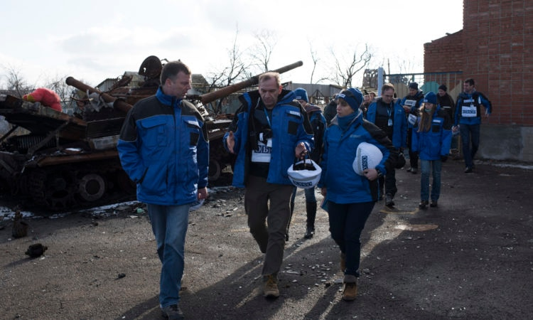Group of OSCE monitors with helmets in hands on foot patrol in Kominternove, Ukraine walking by a tank. (photo: OSCE/Evgeniy Maloletka)