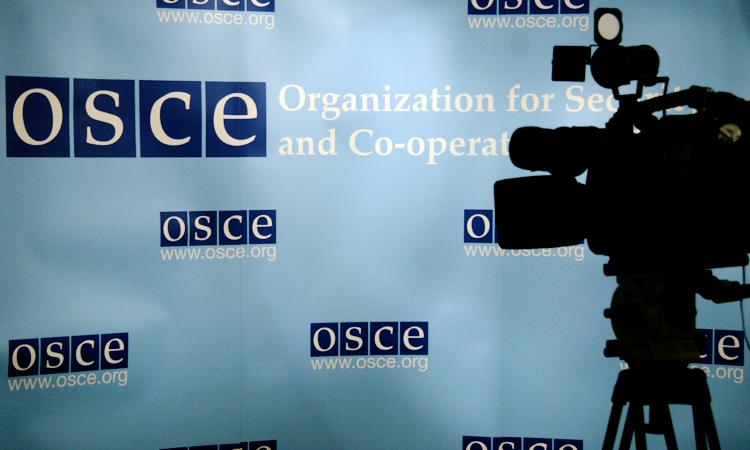 Телекамера, расположенная в передней части заднего плана с логотипами ОБСЕ в преддве́рии пресс-конференции в Хофбурге в Вене. (OSCE, Mikhail Evstafiev)