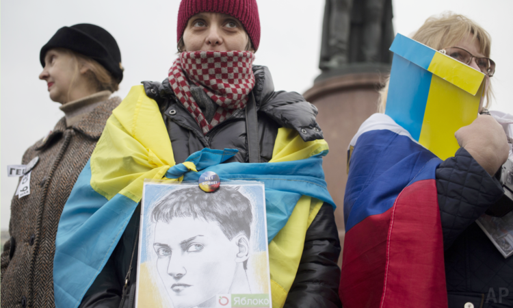 A protester holds a portrait of Ukrainian military officer Nadiya Savchenko during an anti-war rally in Moscow, Russia, Saturday, Oct. 17, 2015. (AP Photo/Pavel Golovkin)