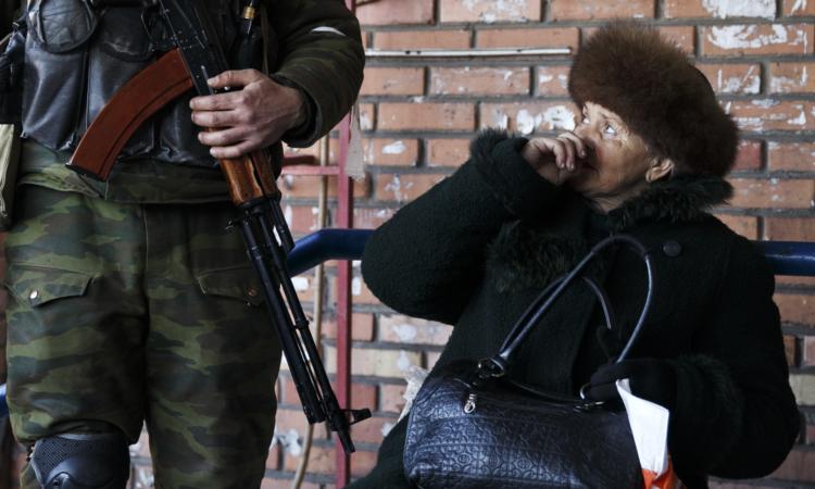 A woman looks at a Russia-backed separatist in Debaltseve, Ukraine, Feb. 23, 2015. (AP Photo/Vadim Ghirda)