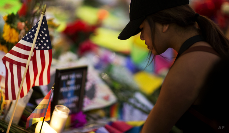 A mourner visits a makeshift memorial for the victims of the mass shooting at the Pulse Orlando nightclub Tuesday, June 14, 2016, in Orlando, Fla. (AP)