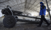 In this March 2015 photo, an OSCE monitor inspects a cannon stored by Russia-backed separatists in eastern Ukraine. (AP Photo/Mstyslav Chernov)