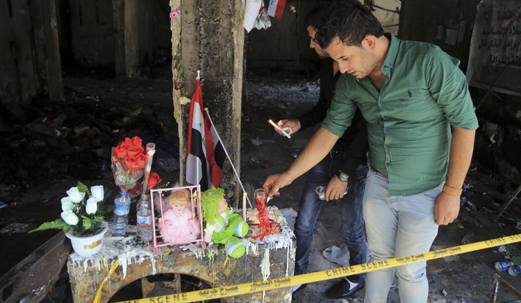 People light candles next to dolls belonging to Rabab Faris, 5, a bomb victim at the scene of a massive truck bomb attack in the Karada neighborhood, Baghdad, Iraq. (AP Photo/Karim Kadim)