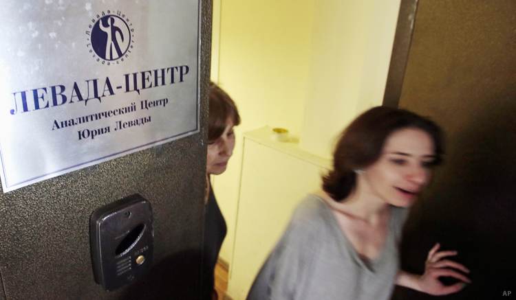 "Levada Center employees leaving their office with the sign ""in Moscow, Russia, in 2013. (AP)"