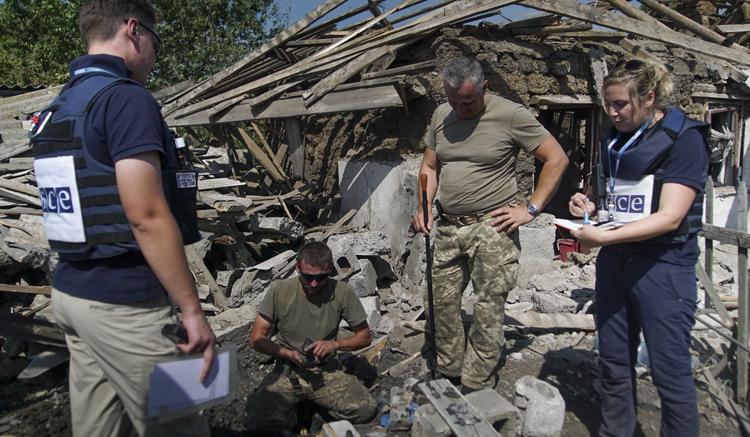 OSCE members monitor territory near a house destroyed by shelling in Solodke village, eastern Ukraine. (AP)