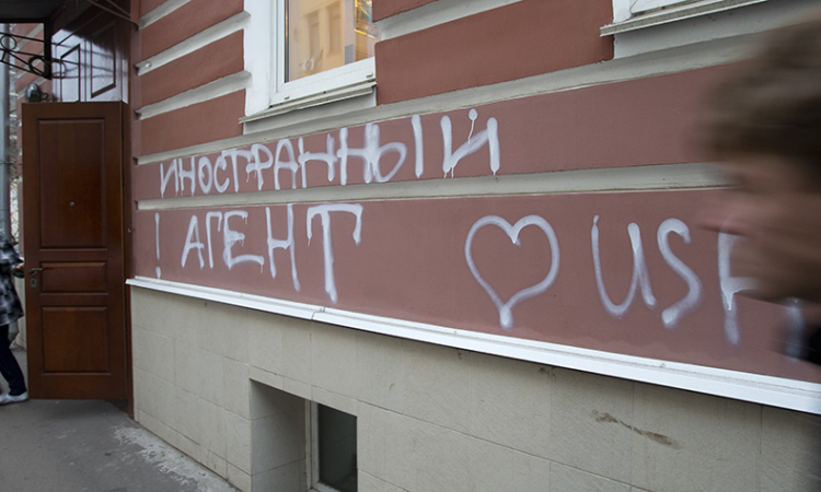 "A man passes by the office of Memorial rights group in Moscow, Russia in 2012. The building has the words ""Foreign Agent (Loves) USA"" spray-painted on its facade. (AP)"