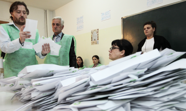 Electoral commission staff count ballot papers after voting closed at a polling station in Tbilisi, Georgia, early Sunday, Oct. 9, 2016. (AP)