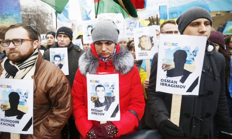 Ukrainian and Crimean Tatar activists hold portraits with the names of victims of the Russia's attempted annexation of Crimea during a rally in Kiev, Ukraine, Sunday, February 26, 2017. (AP Photo/Sergei Chuzavkov)