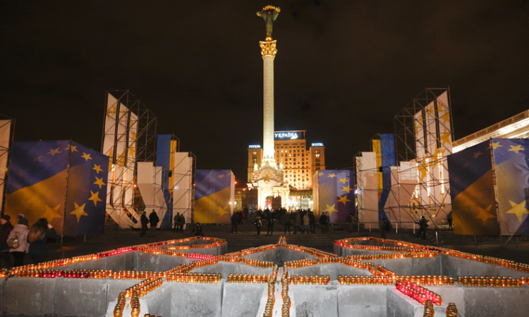 People light candles placed in the shape of Ukraine's coat of arms, to pay tribute to the victims of the 2013-2014 anti-government protests called the Revolution of Dignity, during commemoration events in central Kiev, Ukraine, Tuesday, Nov. 21, 2017. (AP Photo/Efrem Lukatsky)
