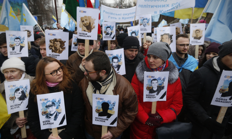 Ukrainian and Crimean Tatar activists hold portraits with the names of victims of Russia's attempted annexation of Crimea, Kiev, Ukraine, Feb. 26, 2017. (AP Photo/Sergei Chuzavkov)