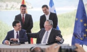 Greek Prime Minister Alexis Tsipras, background right, and his Macedonian counterpart Zoran Zaev, background left, look on as Greek Foreign Minister Nikos Kotzias, right, and his Macedonian counterpart Nikola Dimitrov sign an agreement on Macedonia's new name in the village of Psarades, Prespes Greece, on Sunday, June 17, 2018. (AP Photo/Yorgos Karahalis)