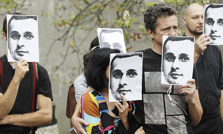 People hold up portraits of Ukrainian filmmaker Oleg Sentsov, who is currently on hunger strike in a Russian jail. (AP Photo/Petr David Josek)