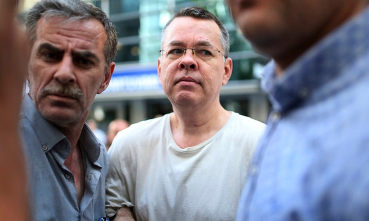 Andrew Craig Brunson, centre, an evangelical pastor from Black Mountain, North Carolina, who had been jailed in Turkey for more than one and a half years on terror and espionage charges, arrives at his house in Izmir, Turkey where he was put under house arrest as his trial continues, July 2018. (AP Photo/Emre Tazegul, File)