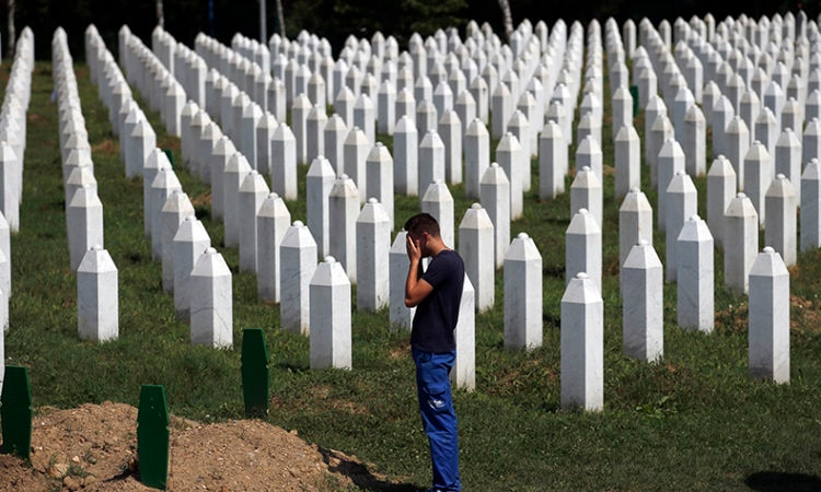 A man prays among gravestones at the memorial centre of Potocari near Srebrenica, 150 kms north east of Sarajevo, Bosnia, Tuesday, Aug. 14, 2018. (AP Photo/Darko Vojinovic)